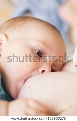 Breastfeeding of seven month baby, closeup chld face - stock photo