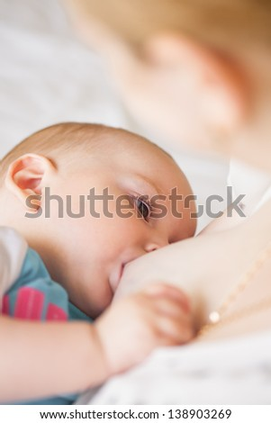 Breastfeeding of seven month baby, play with mother's clothes - stock photo