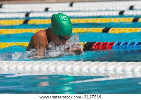 Breaststroke lady with a green cap and goggles - stock photo