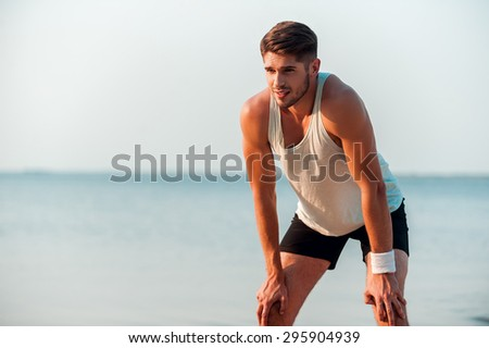 Breathe deep and keep on running. Frustrated young muscular man resting after running while standing at the seaside - stock photo