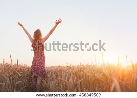 breathing, woman with raised hands enjoying sun in the field - stock photo