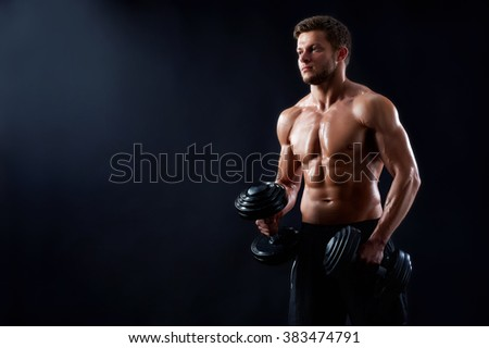 Breathtaking body. Horizontal portrait of a young shirtless fitness man posing with dumbbells showing off his perfect torso copyspace on the side - stock photo