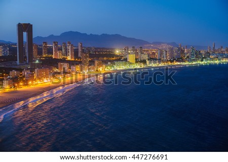 Breathtaking night view of the coastline in Benidorm with high buildings, mountains, sea and city lights