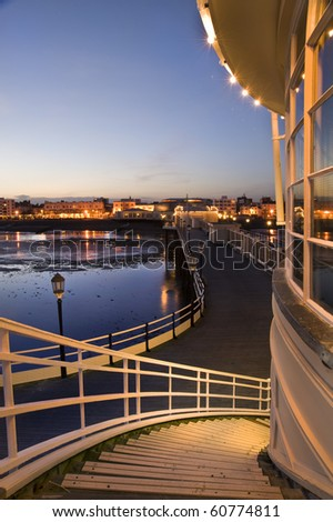 Breathtaking picture along pier back to seafront town alight with glow of evening lights in town - stock photo