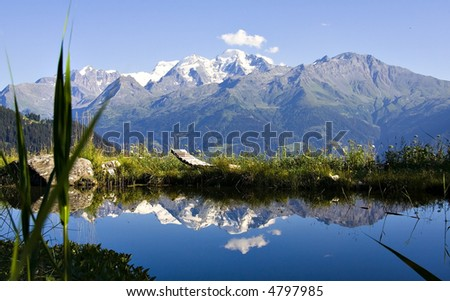 Breathtaking scene of Alpine lake with relax chair. Snowy mountains in background [3]