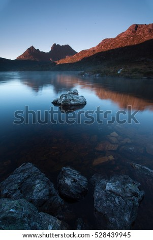 Breathtaking views of Mountain Cradlle National Park in Tasmania. Early morning smoke on water unfolds a mirror reflection of Cradle Mountain peaks in peaceful still waters of ake Dove.