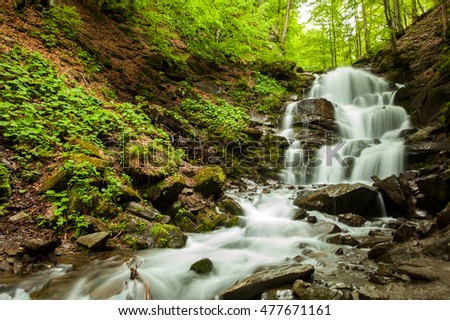 Breathtaking waterfall with stones is falling down on the background of wild nature with green trees.