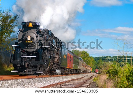 "BRECKSVILLE, OH - SEPTEMBER 14: A vintage steam engine on the Cuyahoga Valley Scenic Railroad, thunders through Brecksville Ohio on September 14 2013. ""Steam in the Valley"" is an annual fall event. - stock photo"