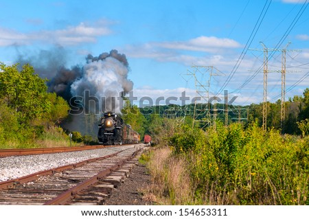 "BRECKSVILLE, OH - SEPTEMBER 14: A vintage steam engine on the Cuyahoga Valley Scenic Railroad, approaches in Brecksville Ohio on September 14 2013. ""Steam in the Valley"" is an annual fall event. - stock photo"