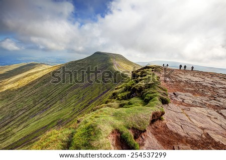 BRECON, WALES - SEPTEMBER 07, 2014 : People walking towards the peak of Pen y Fan from the top of Corn Du in the Brecon Beacons. - stock photo