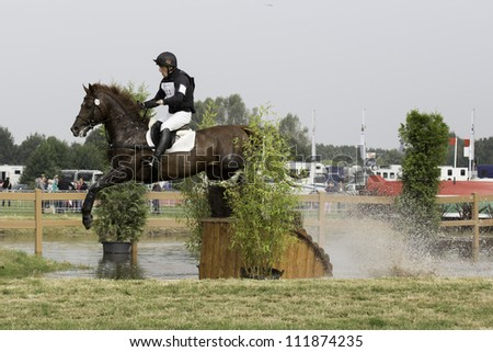 BREDA, HOLLAND - SEPT 2: Jockey Viachaslau Poita on horse jumping over water during yearly cross country contest at Outdoor Brabant, on September 2, 2012 in Breda, the Netherlands - stock photo