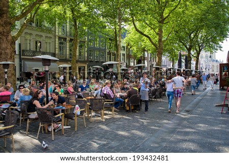 Breda, The Netherlands - May 18: People sitting and relaxing on the main square, the Grote Markt, and drinking a beer , on May 18, 2014 in Breda, Holland - stock photo