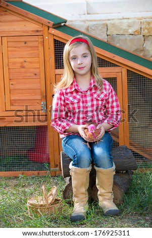 breeder hens kid girl rancher blond farmer playing with chicks in chicken tractor coop - stock photo