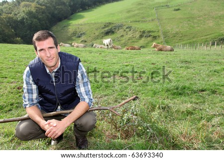Breeder standing in pasture land - stock photo