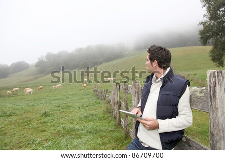 Breeder using electronic tablet in field - stock photo