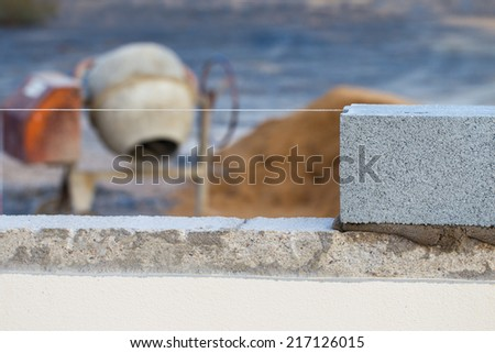 Breeze block wall construction with string line and cement mixer - stock photo