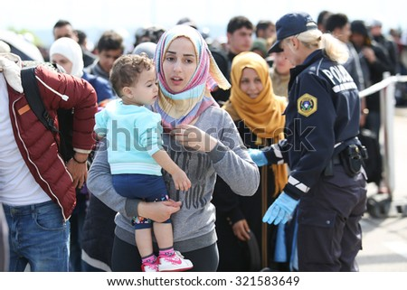 BREGANA, SLOVENIA -SEPTEMBER 20 :A young Syrian woman with a child in her arms walking towards the bus with the other refugees on the slovenian border with Croatia on September 20th,2015 in Slovenia.  - stock photo
