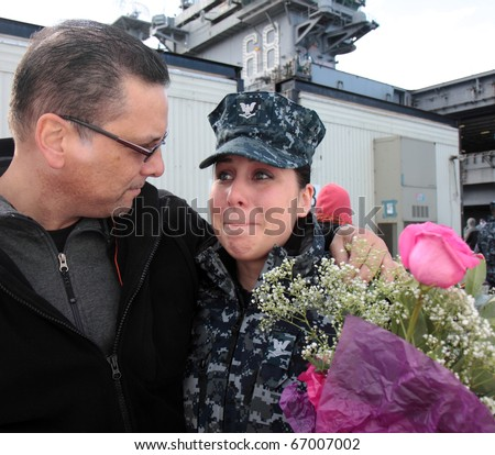 BREMERTON, WA. - DECEMBER 9. A father greets his daughter during her arrival on the USS Nimitz in Bremerton, WA. USA on December, 9th, 2010.  It will be in dry dock for 1 year for maintenance - stock photo