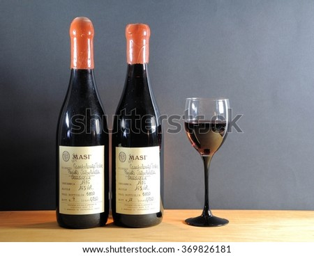 """Brescia, Italy - January 17, 2016: bottles of red wine """"Recioto Valpolicella Amarone"""" produced exclusively in province of Verona, Italy. Limited production of 1976 with numbered  handwritten labels.  - stock photo"""