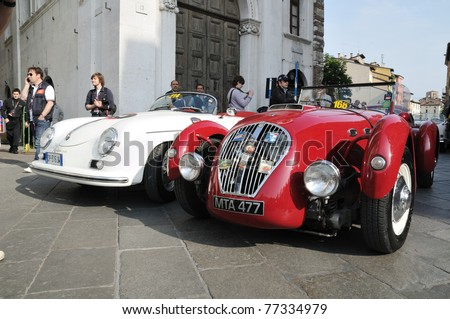 BRESCIA, ITALY - MAY 12 : A 1950 Red Healey Silverstone and a 1955 white Porsche 356 1500 Speedster wait for the sealing (final compliance check) for 1000 Miglia race on May 12, 2011 in Brescia. - stock photo
