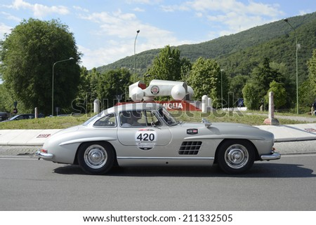 BRESCIA, ITALY - MAY 15: A silver-gray Mercedes 280W Gullwing drives before the 1000 Miglia monument at the 1000 Miglia classic car race on May 15, 2014 in Brescia. This car was built in 1957 - stock photo