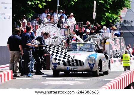 BRESCIA, ITALY - MAY 18: Jochen Mass finishes the 1000 Miglia classic car race on May 18, 2014 in Brescia. The former F1 driver drives a Mercedes 300 SL W Carrera built in 1952 - stock photo