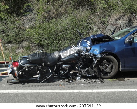 BRESSANONE BRIXEN, APRIL 4, 2011: Severe frontal accident between a motorcyclist and a car. Motorbike Harley Davidson crash collision hit by car on the road in Bressanone Brixen on April 4, 2011 - stock photo