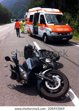 BRESSANONE BRIXEN, MAY 31, 2011: Motorcycle accident that happened on the road after car collision. Injured motorbike rescued by paramedics in Bressanone Brixen on May 31, 2011.  - stock photo