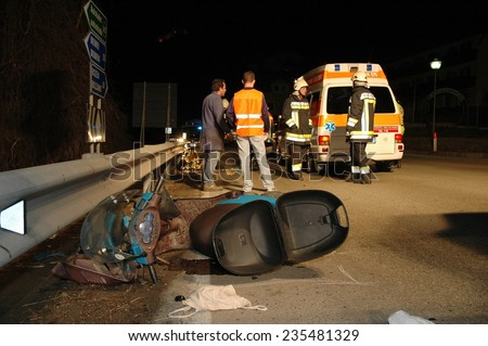 BRESSANONE, ITALY- FEBRUARY 8, 2014: Firefighters and paramedics at work after a traffic accident involving a motor scooter in the night. Crash scooter motorbike on the street on Febraury 8, 2014 - stock photo
