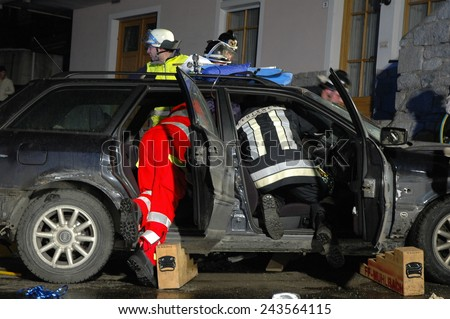 BRESSANONE, ITALY - JANUARY 12, 2015: Firefighters and Paramedics at work in the night inside vehicle after collision between two cars on the road on January 12, 2015. - stock photo