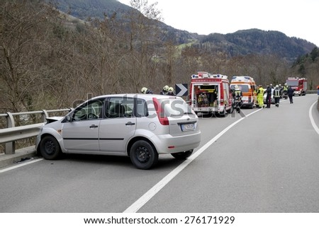 BRESSANONE, ITALY - MAY 8, 2015: Firefighters and Paramedic at work after hard collision between two cars on the road. First aid to injured motorist after car collision on May 8, 2015. - stock photo