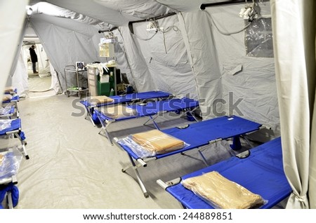 BRESSANONE, ITALY - NOVEMBER 16 2014: Empty hospital field tent for the first AID, a mobile medical unit of red cross. Camp room for the rescue of injured people after flood on November 16, 2014 - stock photo