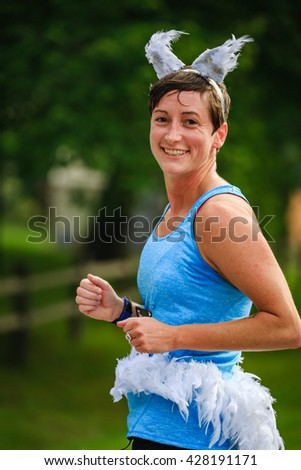 BREVARD, NC-MAY 28, 2016 - Female runner in a white squirrel costume 1 in the White Squirrel Race with over 350 runners in Brevard, NC 2016.  Race is sponsored by Rotary Club of Brevard, NC - stock photo