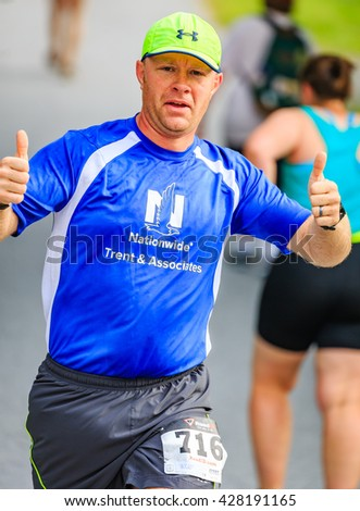BREVARD, NC-MAY 28, 2016 -Happy Man gives a thumbs up as he runs in the White Squirrel Race with over 350 runners in Brevard, NC 2016.  Race is sponsored by Rotary Club of Brevard, NC - stock photo