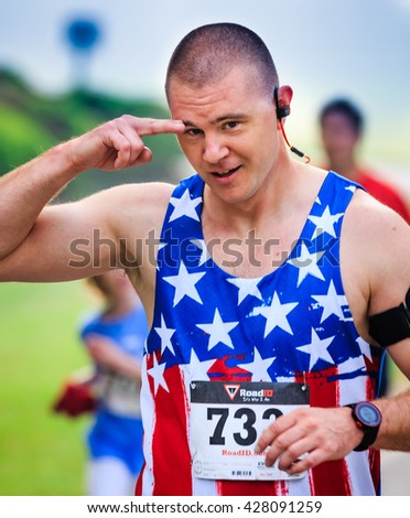 BREVARD, NC-MAY 28, 2016 -Jason Taylor of Camp LeJune, NC salutes as he runs in the White Squirrel Race with over 350 runners in Brevard, NC 2016.  Race is sponsored by Rotary Club of Brevard, NC - stock photo