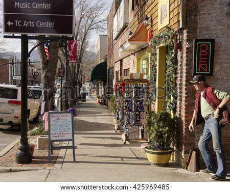 Brevard, North Carolina, USA - December 11, 2015:  Laid back downtown street and man in the small town of Brevard, North Carolina in winter before Christmas on a sunny day,