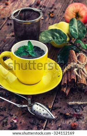 Brew tea.Cup of brewed herbal tea on wooden background strewn with tea leaves - stock photo