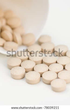 Brewer's Yeast Tablets spilling from bowl, against white background - stock photo