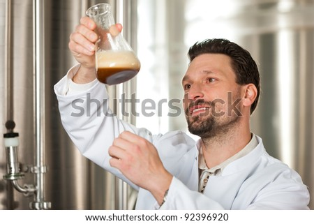 Brewer standing in his brewery and is examining the beer for its purity - stock photo