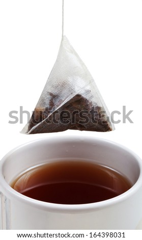 brewing of tea in cup with tea bag close up isolated on white background - stock photo