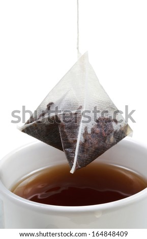 brewing of tea in mug with tea bag close up isolated on white background - stock photo