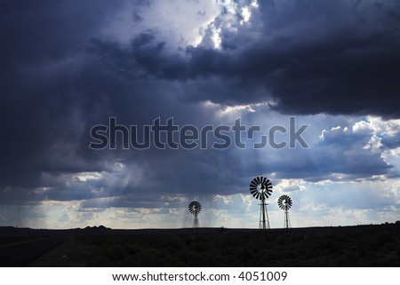 Brewing thunderstorm in the dessert area of the Karoo in South Africa. Three wind pumps silhouetted against the skyline with sunbeams shining through the clouds. - stock photo