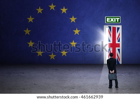 Brexit concept. Male worker wearing formal suit and looking at brexit door with flag of UK and EU