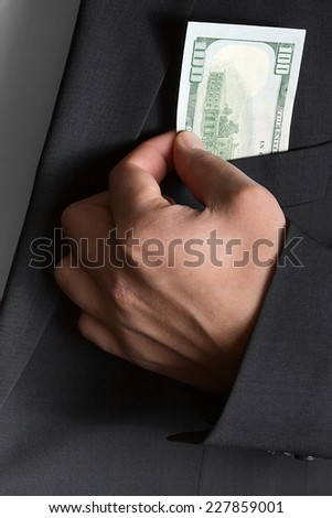 Bribe in businessmen's pocket - stock photo