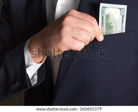 Bribe in businessmen's pocket. One hundred dollars banknote in suit pocket. - stock photo