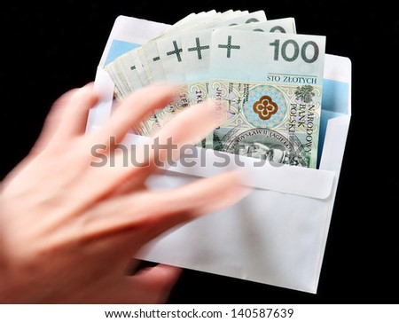 Bribery concept envelope with money and a reaching hand - stock photo