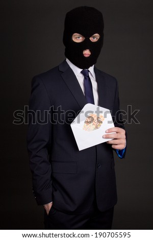 bribery concept - man in business suit and black mask holding envelope with money - stock photo