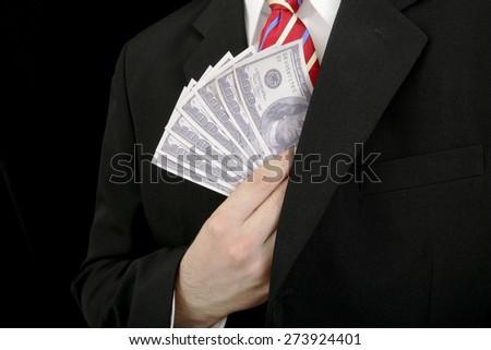 Bribery - man putting US money into jacket pocket - stock photo