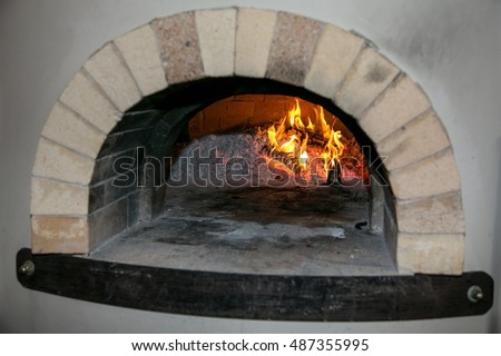 Brick and mortar pizza oven with burning fire