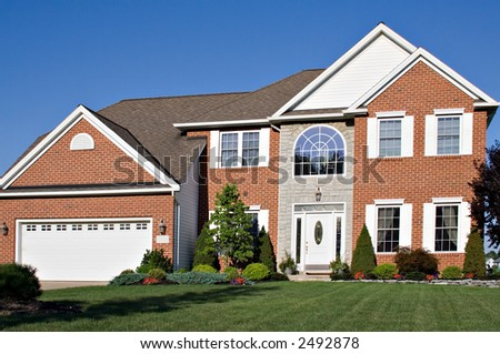 Brick and stone colonial home in the suburbs. - stock photo